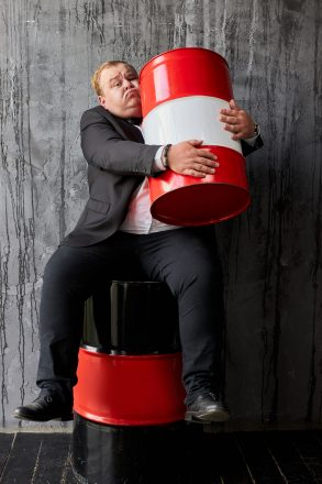 handsome rich caucasian businessman in suit with oil barrel. man sit hugging barrel of oil. business on the extraction of natural resources